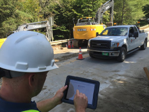 Worker on iPad near truck